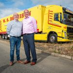 W.S. Dennison Managing Director, William Dennison, with long term Transport Manager, Liam Taggart, standing in front of one of the company's yellow and red anniversary truck and trailers