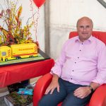 W.S. Dennison Managing Director, William Dennison, sitting next to a yellow and red truck shaped 40th anniversary celebration cake