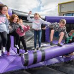 Children boucing on a 'Last Man Standing' inflatable game at WS Dennison's 40th anniversary celebration