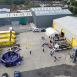 An aerial shot of the W.S. Dennison premises in Antrim showing the 40th anniversary celebration entertainment, including a hog roast, ice cream van, face painting, a portable climbing wall, rodeo bull and two inflatable games