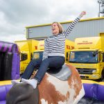 A guest at W.S. Dennison's 40th anniversary celebration having fun on a rodeo bull