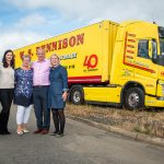 The W.S. Dennison family, from left to right: James, Nikki, Maureen, William and Pamela standing in front of the company's yellow and red truck and trailer which has a special 40th anniversary logo added